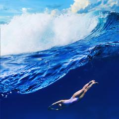 Water sport tropical background Crazy surfer girl diving under big ocean breaking wave