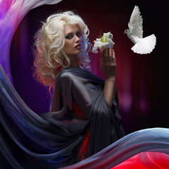 white dove flying close to attractive blonde girl that holding in hands white lily