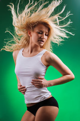 attractive fitness blonde with streamed hair dancing on simple green background