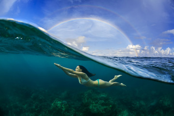 A girl in swimsuit diving under water surface with sky and rainbow above