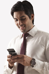 Confident young man text messaging on white background