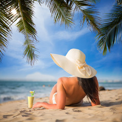 Girl in white hat on a tropical sandy beach with coctail