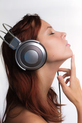 redhead girl with creative make-up in silver headphones listening music at white background