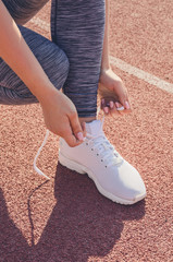 Sport girl workout. Exercise. Fitness. Health. Young girl tying her shoelaces at stadium do some training.