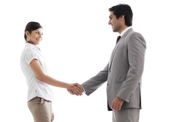 Young business people shaking hands over white background