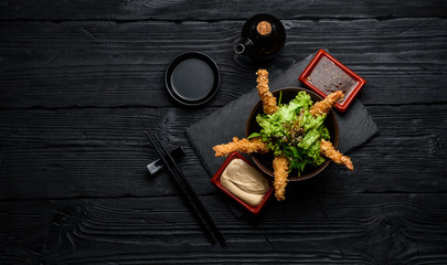 Tempura shrimps with sauces on a dark wooden table