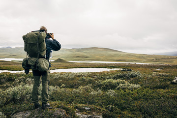 Hiker photographing landscape with smartphone