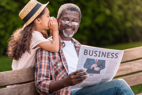 african american girl whispering to her grandfather while he reading business newspaper on bench
