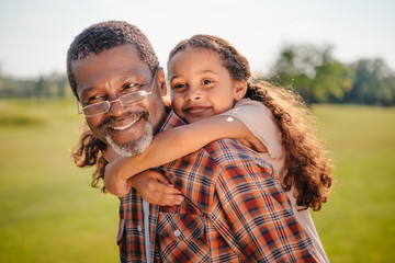happy african american granddaughter hugging her smiling grandfather on green lawn