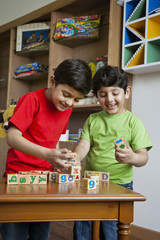 Two little boys playing with wooden toy blocks