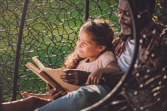 smiling african american girl reading book while sitting in swinging hanging chair with grandfather