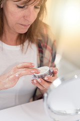 Woman using moisturizer for her face, light effect