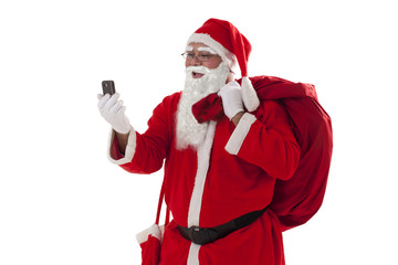 Front view of Santa Claus looking at mobile phone while carrying sack of Christmas presents over white background