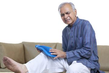 Man holding hot water bottle on knee