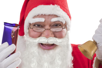Close-up portrait of cheerful Santa Claus showing chocolates with bell and glasses