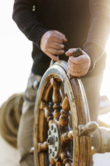 man at the steering wheel of a sailboat