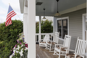 USA, Bangor, Maine. A row of traditional white rocking chairs at the porch of an inn with a stars and stripes flag.