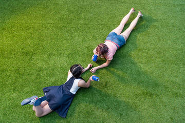 high angle view of multiethnic girls drinking soda from cans while lying on lawn