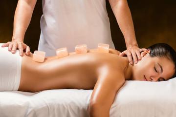 Woman having hot himalayan stone massage in spa.
