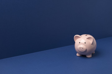 Small Piggy Bank Over Blue Background Copy Space