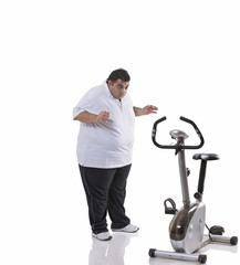 Full length of a shocked obese man looking at an exercise bike over white background