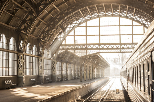 Train station indoor sunset sunrise in sepia. Carriage and platform with construction roof. Travel on train on railway