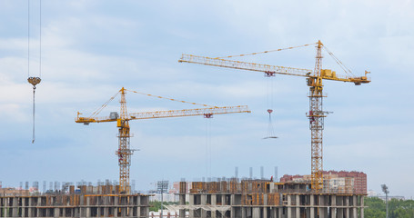 Tower cranes on a background of sky