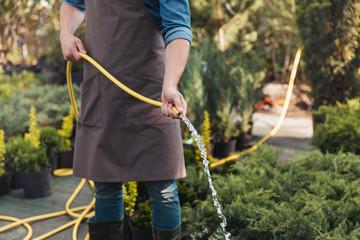 partial view of gardener watering plants with sprinkler in garden