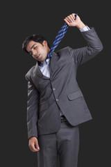 Businessman committing suicide against black background
