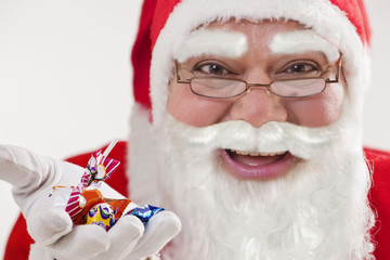 Close-up of happy Santa Claus offering chocolates