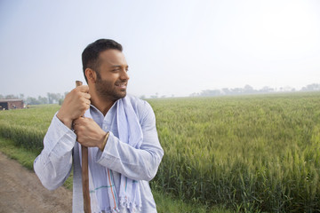 An Indian man looking away while holding a stick