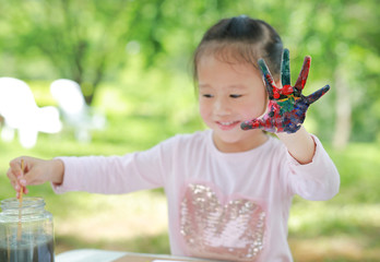 Cute little girl with painted hands in the park, Focus at her hand.