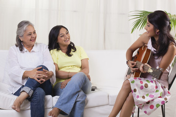 Smiling teenage girl playing guitar for her mother and grandmother