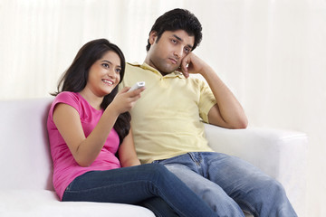 Young woman sitting with bored husband