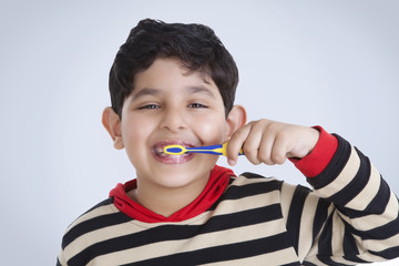 Portrait of little boy brushing his teeth