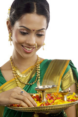 Woman holding a tray with diyas