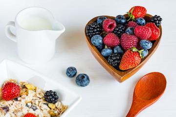 Berries of strawberries, raspberries, blackberries, blueberries in wooden bowl, spoon, jug of milk and muesli on a white wooden table