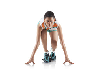 Portrait of young sporty woman at starting block of race isolated over white background