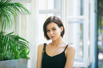 Portrait of young beautiful woman with a short haircut in the city