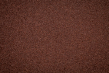 Texture of old dark brown paper background, closeup. Structure of dense umber cardboard