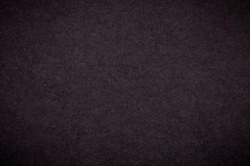 Texture of old dark brown paper background, closeup. Structure of dense black cardboard