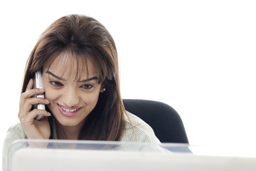 Close-up of beautiful businesswoman using cell phone while looking at computer monitor