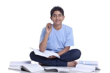 Portrait of teenage boy sitting on floor cross-legged studying against white background