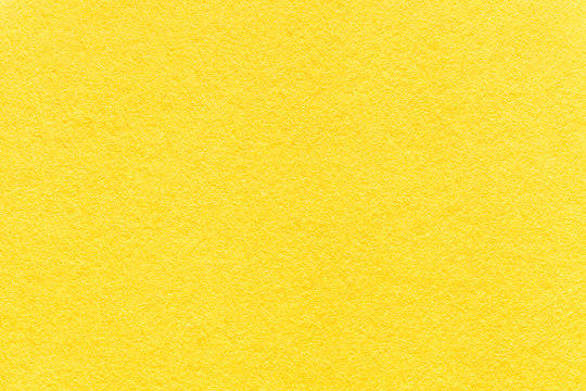 Texture of old light yellow paper background, closeup. Structure of dense lemon cardboard