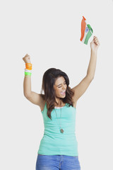 Excited young woman cheering with clenched fists while holding Indian flag over white background