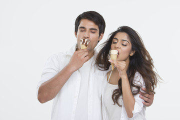 Young couple enjoying ice-cream cones over white background