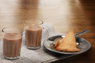 Glasses of chai on newspaper with plate of samosa over a wooden surface