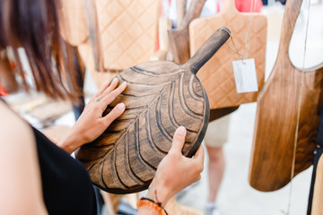 Woman customer choose a handmade wooden board at the sale at the market