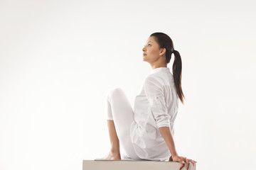 Young woman practicing yoga over white background