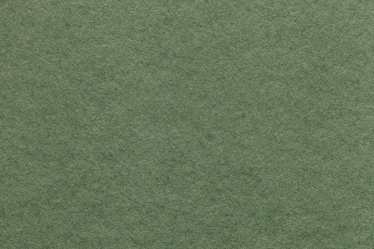 Texture of old light green paper background, closeup. Structure of dense olive cardboard